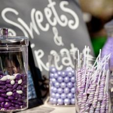 Winter Wedding Sweet and Treats Table With Glass Containers of Purple Colored Candy Varieties