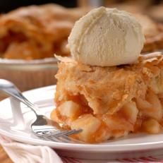 Piece of apple pie with a flaky crust and vanilla ice cream