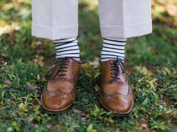 Groom Wears Khaki Pants, Striped Socks and Brown Dress Shoes